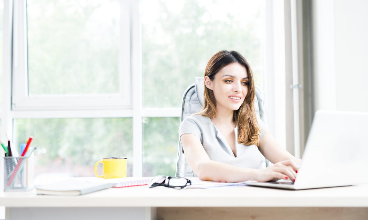 Beautiful Businesswoman Using Laptop in Office